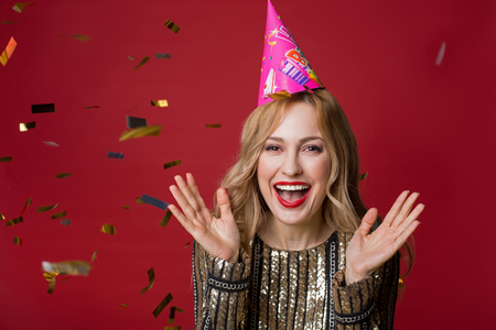 Portrait of contented good looking lady in birthday cone cap standing with raised hands and laughing, surrounded by confetti. Copy space in left side. Isolated on red background 写真素材