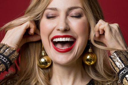 Close up of overjoyed woman trying on new year toys as if it is earrings. Isolated on red background