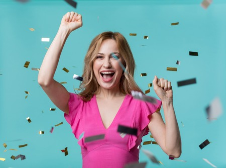 Portrait of contented blonde girl exulting while raising her hands up as gesture of triumph. Confetti flying in air. Isolated on blue background