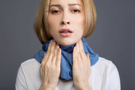 Portrait of sick sad woman in scarf wrapped around her neck, she is touching her throat and looking at camera. Isolated on background