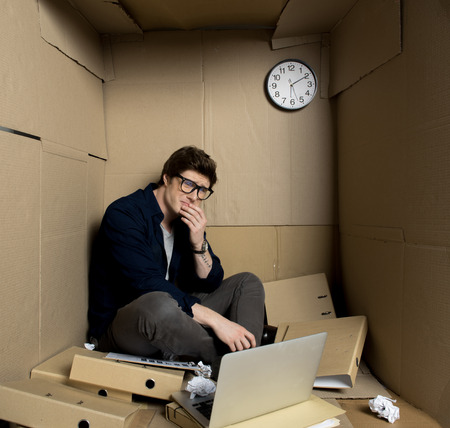 Deep depression concept. Full length of young businessman is sitting with laptop inside his small carton office and crying while touching his face. Crumpled papers and folders are scattered on floor