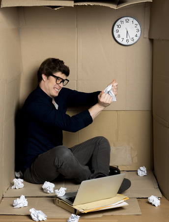 Full of fury. Young businessman is sitting on floor of his cramped carton office and shredding documents with rage. Under stress and lack of space concept Stock Photo