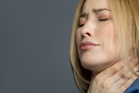 Sick blonde lady holding her hand on neck and wincing in pain. Isolated on background. Copy space in left side