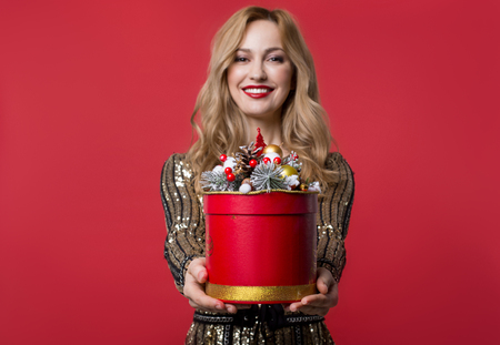 Waist up portrait of smiling girl holding out hands with gift. Isolated on red background