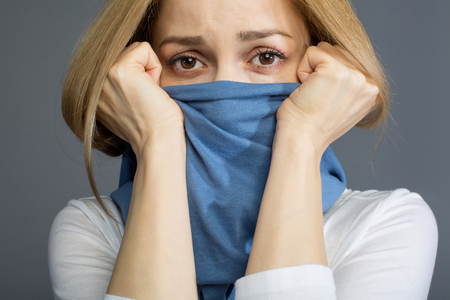 Epidemic concept. Dissatisfied adult woman covering her face with scarf, expressing melancholy. Isolated on background Stock Photo