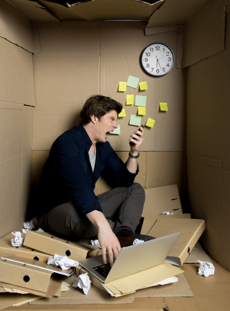 Full of rage concept. Mad employee is sitting on floor inside his confined carton office and yelling on his smartphone while having conversation. Folders and crumpled papers are surrounding him