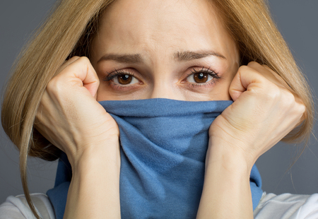 Close up of blonde woman covering her mouth with scarf, her eyes expressing sadness. Isolated on background