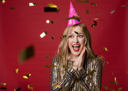Portrait of happy attractive woman in festive clothes standing with clasped hands and laughing, golden confetti flying around. Copy space in left side. Isolated on red background