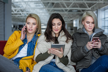 Portrait of three calm women sitting on bench. Everyone is using own device
