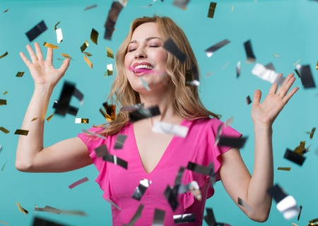Portrait of joyful female standing in cloud of confetti with raised hands and closed eyes. Isolated on blue background