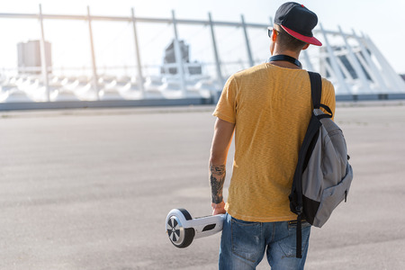 Modern teenager keeping gyroscope in arm while going outdoor. He turning back to camera. Copy space Stock Photo