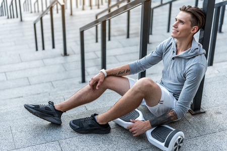 Full length side view happy male athlete resting after exercise at street near hoverboard. Technology concept