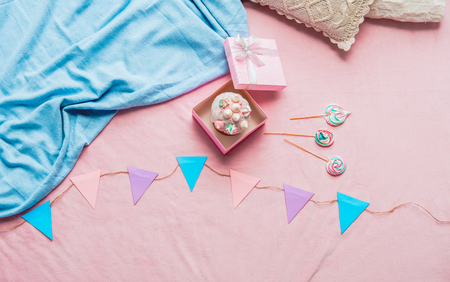 Top view pastry in gift package near sweets and garland with pennants situating on soft rug. Festive concept Stock Photo