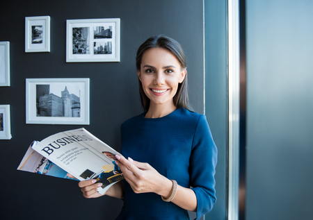 Pleasant relaxation. Portrait of happy elegant attractive businesswoman is standing in cozy office with smile. She is holding open journal and looking at camera with joy