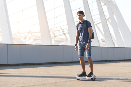 Full length beaming man riding on hoverboard at street. Digital device concept. Copy space