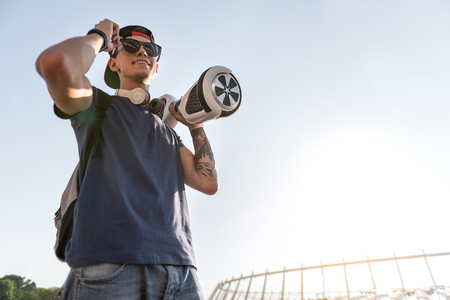 Low angle portrait of beaming teenager holding hoverboard at street. Technology concept. Copy space Stock Photo