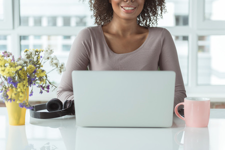 Outgoing girl having job on laptop while situating at desk in office