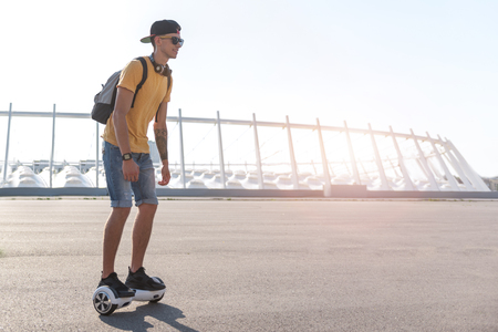 Full length side view cheerful teenager going on hoverboard at street in sunny day. Copy space Stock Photo