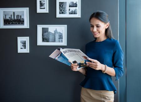 Alegre tiempo de trabajo. Optimista joven elegante está de pie con la revista de negocios y leyendo con placer. Ella está expresando alegría. Copia espacio en el lado izquierdo