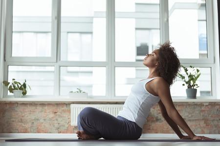 Side view serene girl doing exercise on mat in cozy room. She sitting on floor
