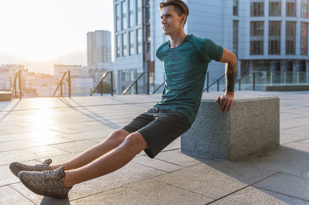 Full length side view outgoing male athlete making exercises at street. Copy space Stock Photo