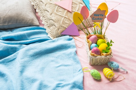 Top view basket with colored eggs locating on pink floor near blue plaid. Easter concept