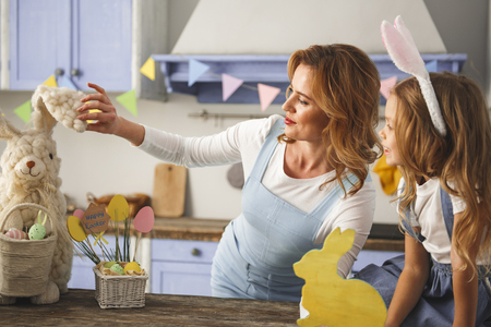 Profile of delighted mother and daughter looking at soft bunny while relaxing in the kitchen decorated for the feast Stock Photo
