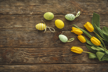 Top view of yellow tulips and fake painted eggs on ligneous board. Copy space in left side Imagens - 96372726