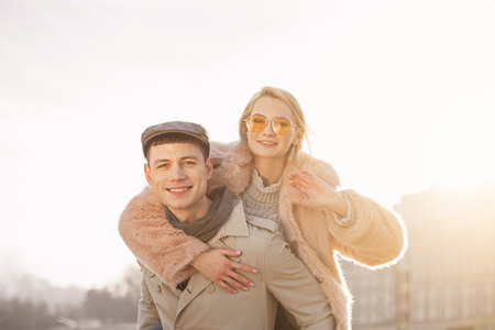 We are team. Portrait of stylish young positive couple are looking at camera with joy while having rendezvous outdoors. Attractive girl is enjoying piggyback ride on man Stock Photo