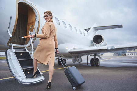 Full length portrait of happy female holding cards and baggage while going upstairs. Journey concept Standard-Bild