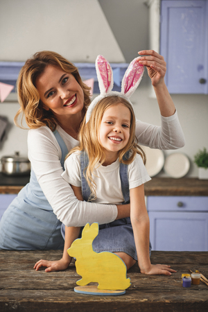 Portrait of mother and daughter standing in the kitchen in a hug. They are looking at camera with pleasure. Decorations are on table