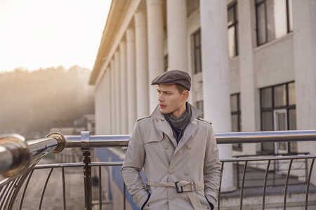Serious young trendy man is standing outdoors while leaning on handrails. He is looking aside with concentration while holding hands in pockets of his coat