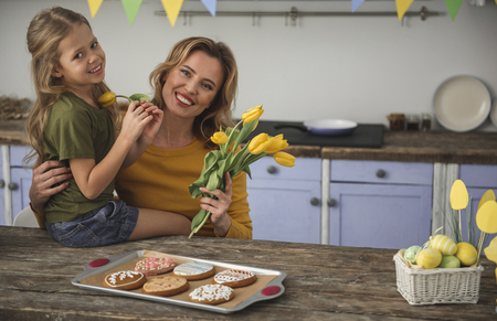 Portrait of young woman and her daughter in kitchen, they are holding yellow tulips and looking at camera with smile. Freshly baked cookies and basket with eggs are on table. Copy space in right side Stock Photo