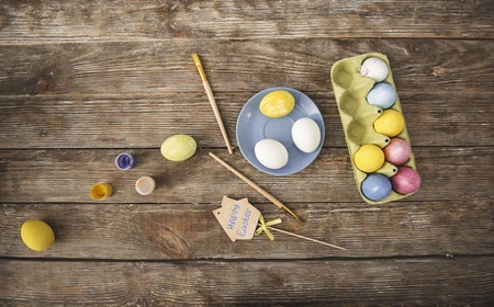 Easter concept. Top view of colored eggs, paint and brushes on wooden table