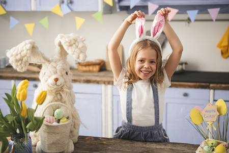 Waist up portrait of smiling kid posing in the kitchen with rabbit ears on head. Colored eggs and toy bunny standing on the table Stock Photo