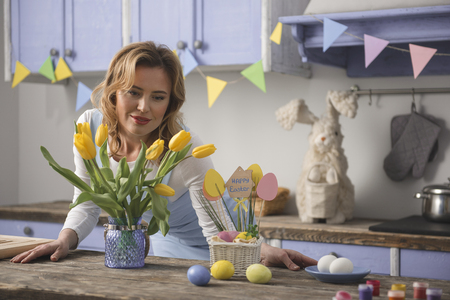 Holiday preparation. Portrait of serene female person standing in the kitchen and looking at flowers in a vase. Copy space in right side Stock Photo