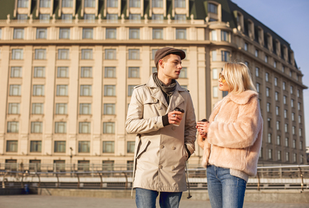 Coffee time. Pleasant young man and woman are standing on square while drinking espresso. They are looking at each other with admiration. Copy space in the left side
