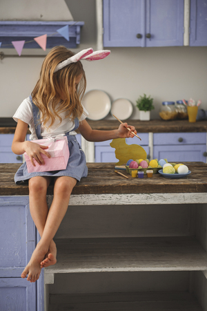 Calm little girl sitting on wooden table indoors. She is colorizing easter eggs with one hand and holding present with another one. Copy space in right side Imagens - 96372938