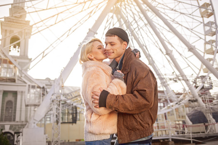 First kiss. Low angle of romantic enamored couple is hugging while standing on street. Charming girl is feeling passion while going to kiss guy. Ferris wheel on background Stock Photo
