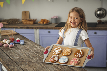 Portrait of smiling little girl standing near wooden kitchen table and demonstrating salver with easter dessert. Copy space in left side Reklamní fotografie - 96372952