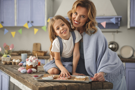 Portrait of woman and her daughter preparing easter confection. They are looking at camera and smiling. Copy space in left side