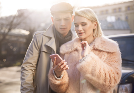 Useful device. Selective focus of modern mobile phone in hand of young charming girl who is standing with her boyfriend outdoors. They are looking at screen of gadget with interest