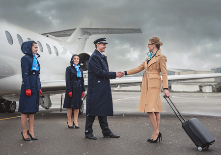 Full length outgoing lady greeting with glad pilot. Optimistic air-hostesses standing near aircraft. Airport and career concept Stock Photo