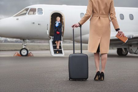 Female going to airplane while holding baggage in hand. Happy air-hostess waiting for her. Occupation concept