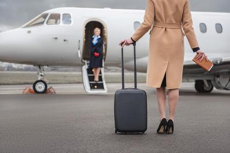 Hembra que va al aeroplano mientras que sostiene equipaje disponible. Feliz azafata esperándola. Concepto de ocupación