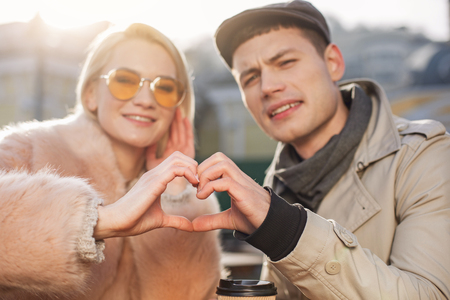 Amour. Close up of young stylish man and charming woman are making heart shape with their hands outdoors. They are looking at camera on background. Selective focus Imagens