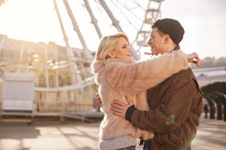 Happy day. Profile of young enamored couple are standing on street and hugging while looking at each other with passion. Copy space in the left side Stock Photo