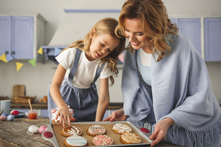 Satisfied mother and daughter standing in the kitchen and looking at cookies prepared for easter