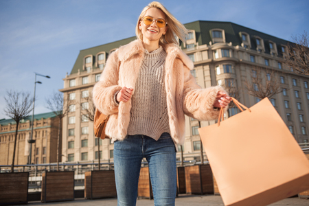 Sunny day. Low angle portrait of stylish attractive young woman is standing on square and holding her shopping bag. She is looking at camera with joy