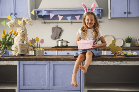 Portrait of glad little girl wearing rabbit ears on head resting in the cozy kitchen with present in hands. Copy space in left side